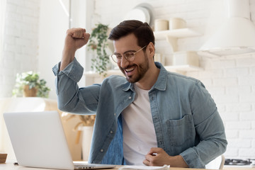 Excited young man looking at laptop celebrating online victory