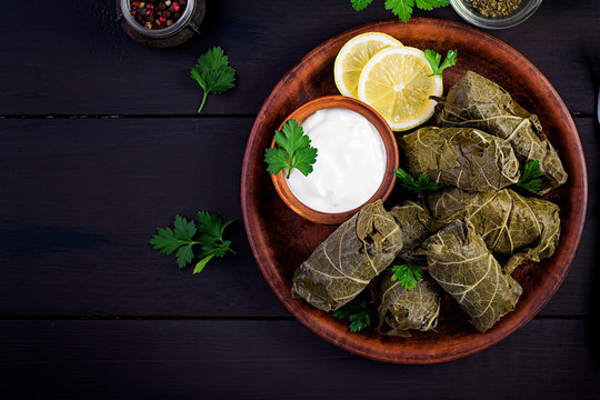 Dolma. Stuffed grape leaves with rice and meat on dark table. Middle eastern cuisine. Top view, overhead, copy space