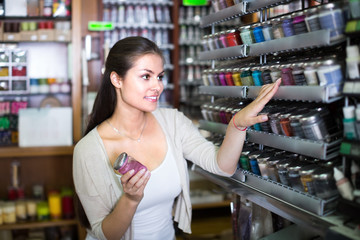 Smiling woman shopping color in glass jar