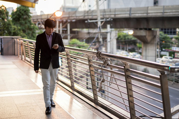 Asian Korean ceo businessman, 40s years old or middle age man, walk on skywalk and check business project plan and chat by smartphone outside office at sunset. Text on mobile phone in modern city.