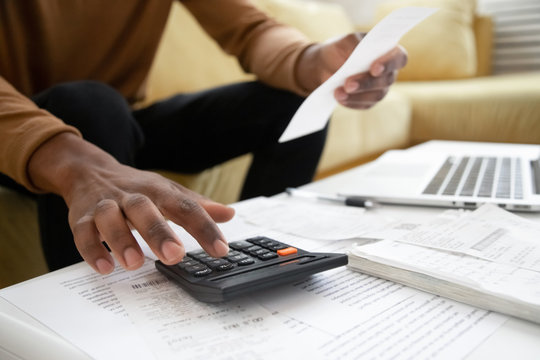 African American man calculating on machine accounting expenses