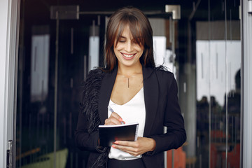 Wall Mural - Beautiful woman working. Busineswoman in a stylish clothes. Woman standing near window with notebook