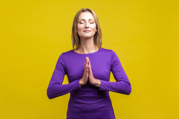 Harmony of mind. Portrait of elegant woman in purple dress standing with closed eyes and peaceful calm face meditating, holding hands in prayer. indoor studio shot isolated on yellow background
