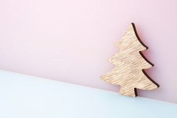 decorative wooden fir tree on pastel pink-blue background, christmas toy, holiday tree, concept christmas, stock photo for a holiday card, place for inscriptions, new year poster