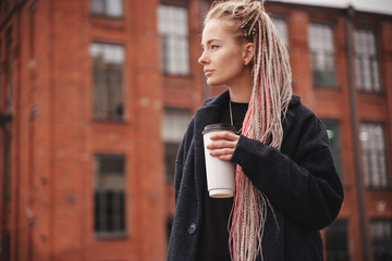 Stylish beautiful young blonde girl with pink dreadlocks with a white glass of take-away coffee, closeup portrait, beauty and fashion concept, trends of millennials and hipsters,