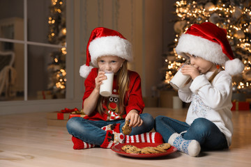 Cute little children drinking milk in living room. Christmas time