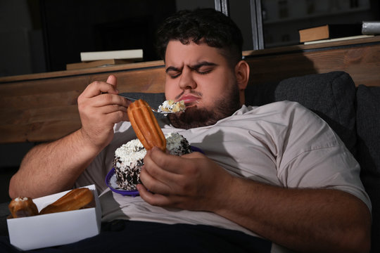 Depressed overweight man eating sweets in living room at night