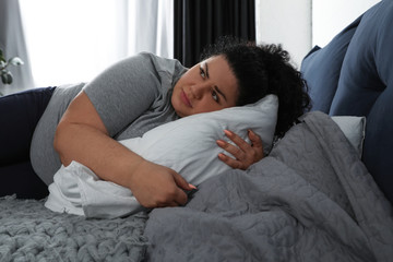 Depressed overweight woman hugging pillow on bed