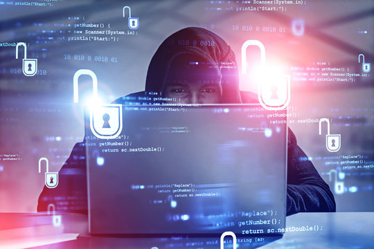 Young hacker with laptop in office, cyber security
