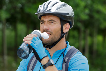 close view of male cyclist drinking water