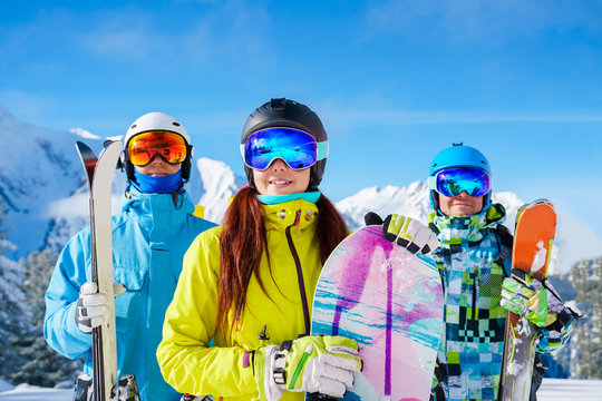 Sportsmen and woman with snowboard and skis standing on snow resort against backdrop of mountain.