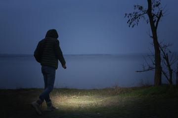 Foto auf Acrylglas Schwarz Man with flashlight walking near river in evening