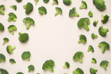 Fresh tasty broccoli on light beige background, flat lay. Space for text