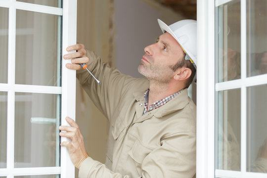 a construction worker fixing a window