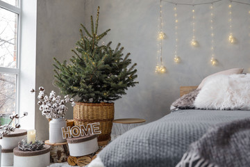 Little Christmas tree with fairy lights in bedroom interior
