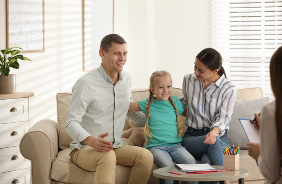 Family on appointment with child psychotherapist indoors