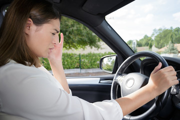 woman having headache in a car