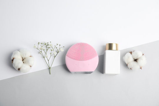 Flat lay composition with face cleansing brush on color background. Cosmetic accessory