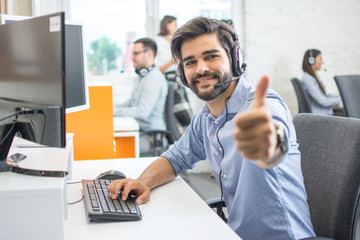 Smiling call center operator in headset looking at camera and showing thumb up