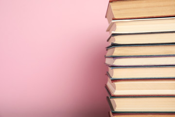 Stack of hardcover books on pink background. Space for text