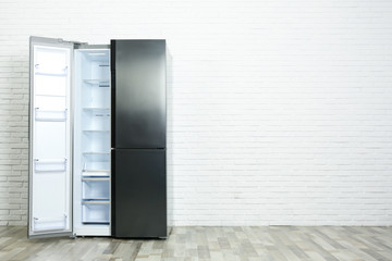 Modern empty refrigerator near white brick wall, space for text