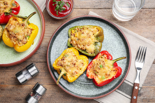 Tasty stuffed bell peppers served on wooden table