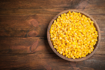 Delicious canned corn in bowl on wooden table, top view. Space for text