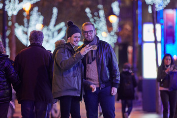 homosexual couple of boys, shopping, at Christmas, at night, they will click on the smartphone the photo they have taken