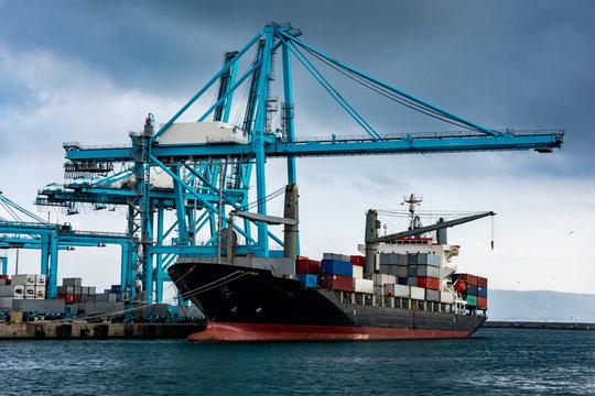 Barco porta contenedores en el puerto con las gruas preparadas para trabajar
