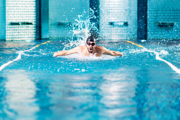 professional swimmer doing exercise in indoor swimming pool