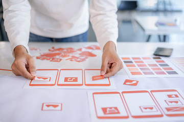 Cropped shot of creative UX UI designers team designing, Developing mobile application from prototypes and wireframe layout. Mobile application developer workplace concept.