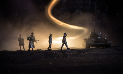 Battle scene. Military silhouettes fighting scene on war fog sky background. A German soldiers raised arms to surrender. Plastic toy soldiers with guns taking prisoner the enemy soldier.