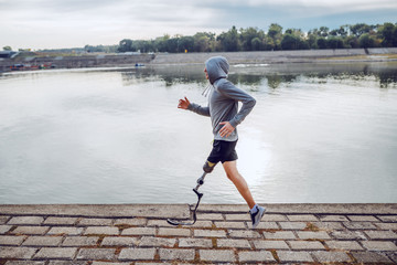 Fotomurales - Side view of healthy caucasian handicapped sportsman in sportswear and with artificial leg running on quay.