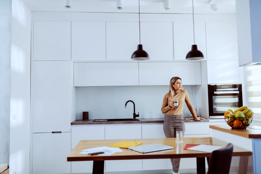 Attractive caucasian blonde fashionable woman leaning on kitchen counter, holding mug with coffee and looking trough window.