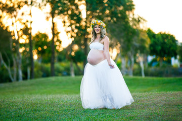 Happy pregnant woman with long hair  on a sunny day, beach and park