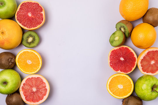 Slice of Grapefruit Orage Kiwi on Blue Background Fruit Background Frame Copy Space Vitamin Detox or Diet Concept Flat Lay