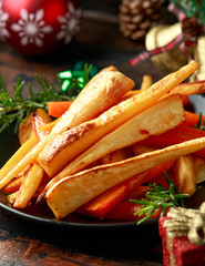 Christmas Roasted Parsnips and Carrots with decoration, gifts, green tree branch on wooden rustic table