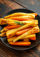 Roasted Parsnips and Carrots with herbs on rustic wooden table