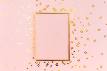 Photo frame mock up with space for text, golden confetti on a pink background. Colorful celebration, birthday background.Christmas or New Year pattern. Flat lay, top view