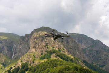 Drone with camera flying over mountain fields.