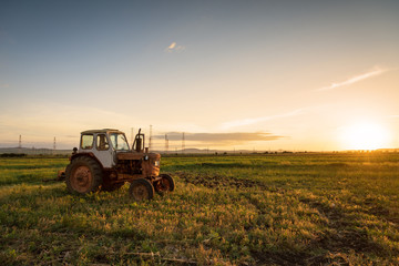 Red tractor on golden sunset sky.