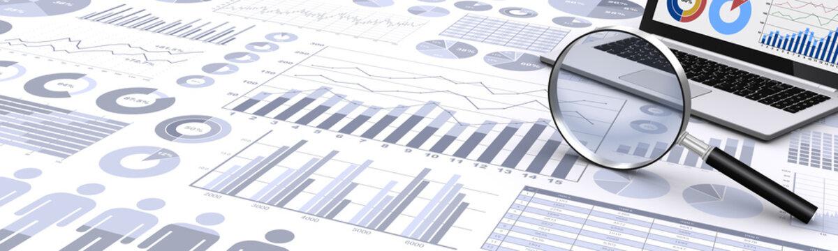 ビジネス資料と虫眼鏡、ノートパソコン