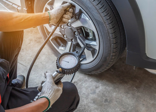 Close up mechanic inflating put air into the tyre and checking air pressure with gauge pressure in service station
