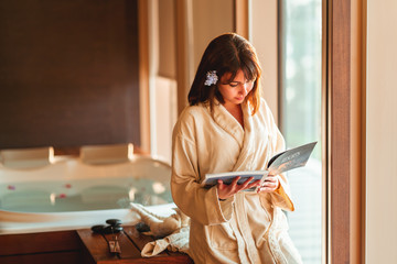 woman reading magazine while waiting for massage at spa center