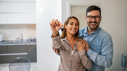 Young couple holding the keys for their new home. Couple holding a house key in their new home. They are standing in their new modern house. Both are happy and smiling.