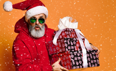Popular elderly man an old men in a Santa Claus hat happy walks with New Year's gifts with a gray...