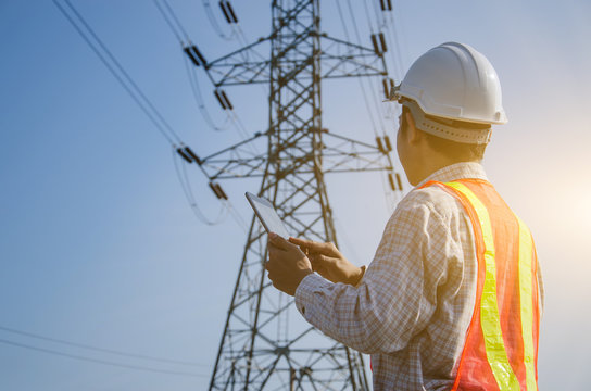 Electrical engineer holding and using a digital tablet with high voltage tower background.