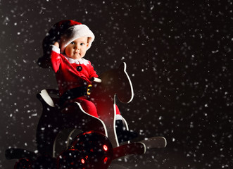 Little toddler boy in santa claus costume and hat rides a wooden horse for children swing with new year gift boxes