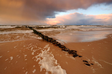 Piękne wybrzeże Morza Bałtyckiego o zachodzie słońca,fale oblewają falochron na piaszczystej...