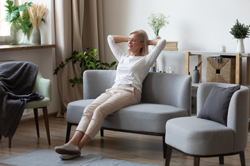 Attractive elderly woman resting on couch putting hands behind head